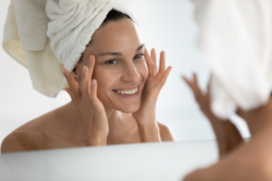 woman looking at face in mirror smiling