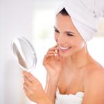 woman with beautiful skin looking in mirror